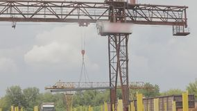 Lading van metaalproducten door een brugkraan, het werk van een brugkraan in productie, een kraan in een pakhuis
