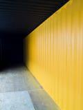 Ladingscontainer diep aan dark met gele muur Royalty-vrije Stock Foto's