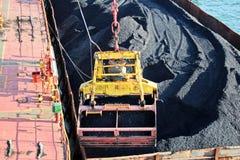 Ladingssteenkool van ladingsaken op een bulk-carrier die schipkranen en grepen gebruiken bij de haven van Samarinda, Indonesië stock foto