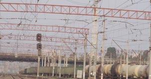 Ladingstrein die door met veel torens met hoog voltage op spoorweg overgaan stock video