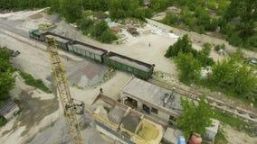 Ladingstrein die industrieel puin dragen bij oud concreet fabrieks luchtschot stock video