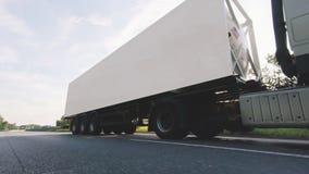 Ladingsvrachtwagen met ladingsaanhangwagen het drijven op een weg