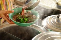 The ladle is drained in a bowl of noodles,Cooking noodle in thai. Land,the noodles pork and beef Royalty Free Stock Image