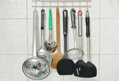 Ladle flipper and colander with other kitchenware mobile on stainless hanger in kitchen Royalty Free Stock Photos