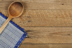 Ladle and tablecloth. Wooden ladle and folded tablecloth on wooden surface Royalty Free Stock Photography