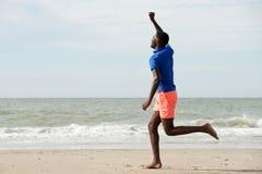 Lado completo do comprimento do homem novo feliz que corre na praia com os braços aumentados imagem de stock