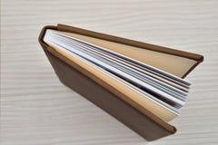 Lado de casarse el álbum de foto de cuero marrón entornado en b de madera blanco imágenes de archivo libres de regalías