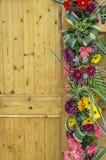 Lado de la puerta de madera adornado con las flores Foto de archivo libre de regalías