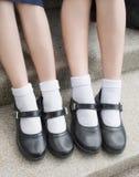 Lado de las piernas y de los pies tailandeses asiáticos del estudiante de la colegiala de las muchachas con los zapatos negros Foto de archivo