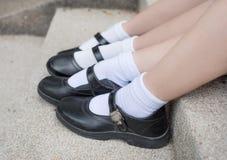 Lado de los pies tailandeses asiáticos del estudiante de la colegiala de las muchachas con los zapatos negros Foto de archivo