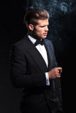 Lado de un hombre de la moda en el smoking que fuma un cigarro Foto de archivo