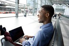 Lado del hombre de negocios afroamericano que espera en la estación con el ordenador portátil fotos de archivo