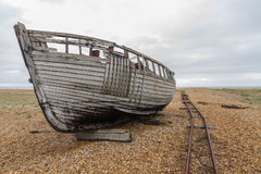 Lado do barco abandonado velho com os trilhos em Pebble Beach Fotografia de Stock