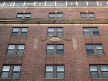 Lado do edifício de tijolo vermelho com emblema clássico Fotografia de Stock Royalty Free