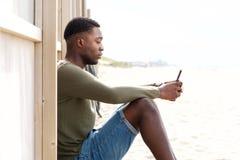 Lado do homem negro novo considerável que senta-se fora com telefone celular fotos de stock royalty free