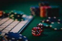 Lado rojo del póker en foco Vista lateral de una tabla verde del póker con algunas fichas de póker en un teclado Jugar el apego e fotos de archivo