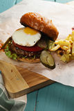 Lado soleado encima de la hamburguesa en un tablero de la mesa de madera Imágenes de archivo libres de regalías