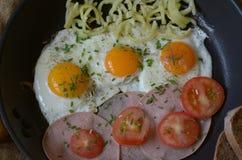 Lado soleado encima de los huevos con las cebolletas, los tomates, la pimienta y el salami Imagen de archivo