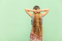 Lado trasero Blonde joven hermoso con el pelo largo, cabeza cruzada del onder de las manos Imagen de archivo