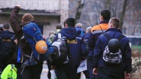 Lado trasero de hombres jovenes que caminan en chaquetas del emercom con las mochilas calle metrajes