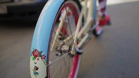 Lado trasero de la muchacha que completa un ciclo en rueda del día de verano de un foco de la bicicleta adentro Cámara lenta almacen de metraje de vídeo