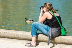 Lado trasero de la mujer joven que toma una foto Imágenes de archivo libres de regalías