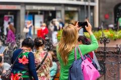 Lado trasero de la mujer joven que toma una foto con su teléfono Imágenes de archivo libres de regalías