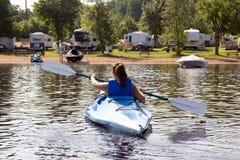 Lado trasero de una mujer kayaking en un lago tranquilo Imagen de archivo libre de regalías