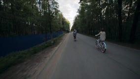Lado trasero del grupo de personas de ciclo en un parque por la tarde del verano Cámara lenta metrajes