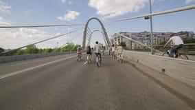 Lado trasero del grupo de personas de ciclo a través del puente en día del cloudness del verano almacen de metraje de vídeo
