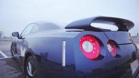 Lado trasero del nuevo coche azul marino del cupé en la calle parachoques presentación Luces rojas automóvil Sombras frías almacen de metraje de vídeo