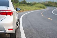 Lado trasero del nuevo estacionamiento de plata del coche en la carretera de asfalto Foto de archivo