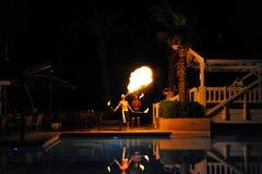 Lado, Turquía - 10 de abril de 2014: El artista de la demostración del fuego respira el fuego en la oscuridad en un hotel de lujo foto de archivo