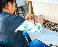 Lado, Turquia - 24 de maio de 2015: Uma mulher não identificada tece uma carpa Imagens de Stock