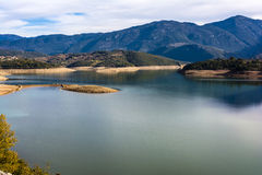 Ladonas artificial lake in Greece against a blue sky with clouds, and mountains as background. Ladonas artificial lake in Arcadia, Greece against a blue sky with Royalty Free Stock Photography