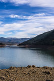 Ladonas artificial lake in Greece against a blue sky with clouds, and mountains as background Stock Image