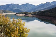 Ladonas artificial lake in Greece against a blue sky with clouds, and mountains as background. Ladonas artificial lake in Arcadia, Greece against a blue sky with Royalty Free Stock Images