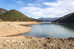 Ladonas artificial lake in Greece against a blue sky with clouds, and mountains as background. Ladonas artificial lake in Arcadia, Greece against a blue sky with Stock Image