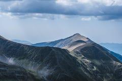 Lados escuros e ensolarados de cumes da montanha da opinião do pico de Moldoveanu A tempestade está vindo imagens de stock royalty free