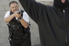 Ladrão de Aiming Gun At do agente da polícia Fotos de Stock Royalty Free