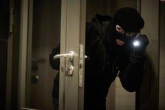 Ladrão do assaltante na máscara Arrombamento de um apartamento imagem de stock