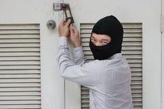Ladrão mascarado que usa uma ferramenta da colheita do fechamento à quebra e a participar em uma casa Conceito criminoso do crime imagens de stock royalty free
