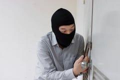 Ladrão mascarado que usa uma ferramenta da colheita do fechamento à quebra e a participar em uma casa Conceito criminoso do crime imagem de stock royalty free