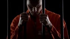 Ladrão na cadeia que sente o pesar sincero do crime, guardando barras da prisão em desesperado foto de stock royalty free