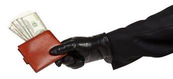 Ladrão no terno preto que guarda uma bolsa de couro marrom com dólares Foto de Stock