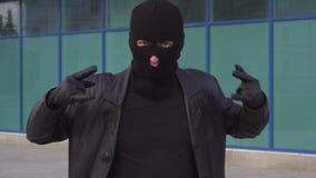 Ladrão ou ladrão criminoso do homem no og do sinal da exibição da máscara os chifres na câmera video estoque