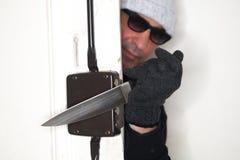 Ladrão que olha fora de uma porta Imagem de Stock