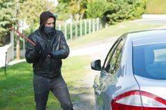 Ladrão que rouba um carro Fotos de Stock Royalty Free