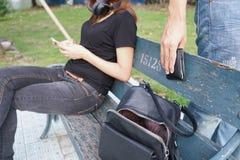 Ladrão que tenta roubar e andar afastado a carteira no saco quando woma imagens de stock