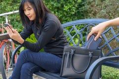 Ladrão que tenta roubar e andar afastado a carteira quando utilização da mulher fotos de stock